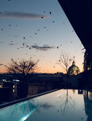 Der Sonnenuntergang über den Dächern Wiens spiegelt sich im Grand Ferdinand Rooftop Pool.
