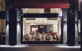 Der Blick von der Ringstraße ins Grand Ferdinand Restaurant mit gedeckten Tischen.