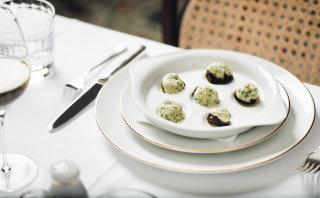 Wiener Schnecken mit Kräuterbutter überbacken und serviert auf edlem weißen Porzellan.