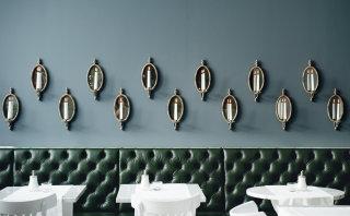 Kerzenbestückte Wand in der Grand Étage mit dunkelgrünen Polstermöbeln.