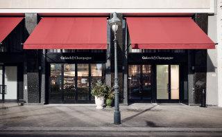 Der Eingang zum Gulasch & Champagne auf der Ringstraße mit heruntergelassenen roten Markisen.