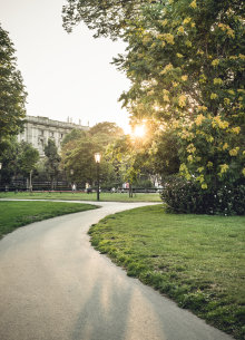 Pathway through the park in front of the Hofburg at dusk.