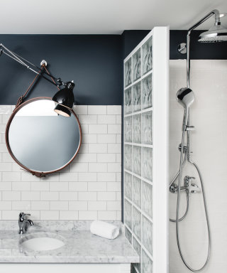 Rain shower with glass wall, washbasin and mirror with leather frame.