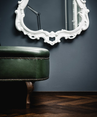 Mirror with curved white frame and dark green leather chaiselongue.