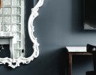 Spiegel mit geschwungenem Rand in Weiß und Schreibtisch im Business Zimmer.