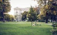 Im Park vor dem Kunsthistorischen Museum liegt ein Pärchen in der Wiese und entspannt sich.