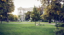 A couple is relaxing in the grass at the park in front of the Hofburg.