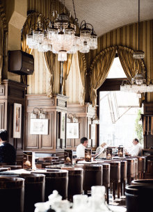 Coffee house in Vienna with classic wood paneling, chandelier and leather chairs.