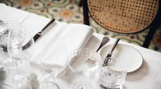 Gedeckter Tisch im Grand Ferdinand Restaurant mit Champagnerglas und Silberbesteck.