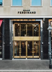 The entrance to Grand Ferdinand with golden wing doors.