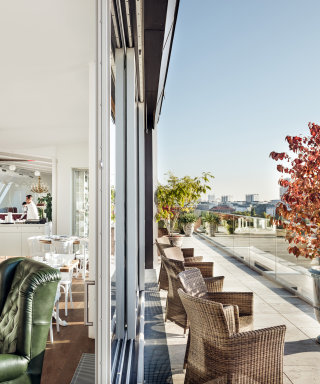 The Grand Ferdinand rooftop terrace with comfortable rattan chairs.