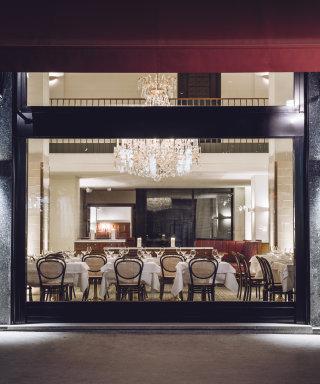 Blick ins Grand Ferdinand Restaurant mit gepolsterten Holzstühlen, weißen Tischdecken und Luster.