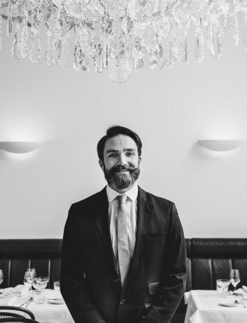 Lächelnder Mitarbeiter im Grand Ferdinand Hotel mit Anzug und Krawatte.