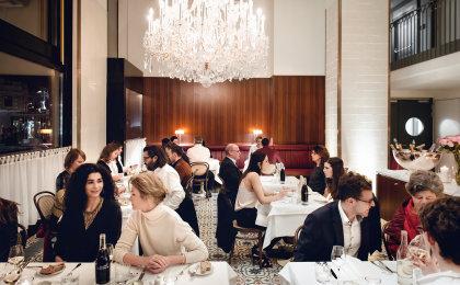 Volle Tische im Grand Ferdinand Restaurant am Abend, mit hell erleuchtetem Lobmeyr Luster.