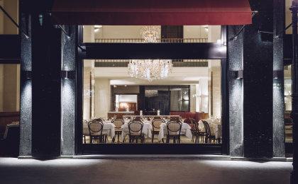 Grand Ferdinand Restaurant mit gepolsterten Holzstühlen und weißen Tischdecken.