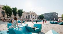 Menschen entspannen auf türkisen Sitzgelegenheiten am Platz des MuseumsQuartiers.