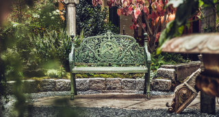 Dainty bench in the middle of a tropical garden in the courtyard.