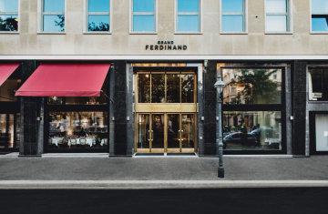 Außenansicht vom Grand Ferdinand Eingang mit goldenen Flügeltüren und roter Markise .
