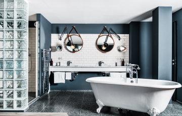 Die Grand Ferdinand Suite mit rundem Spiegel mit Lederrahmen und freistehender Badewanne.