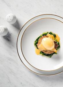 Fleischlaberl auf Blattspinat mit pochiertem Ei serviert im Porzellanteller.