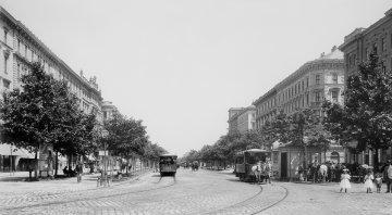 Historische Ansicht der Ringstraße mit Straßenbahnen und Baumallee.