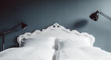 Kingsize-Bett mit geschwungenem Betthaupt und weißer Bettwäsche.