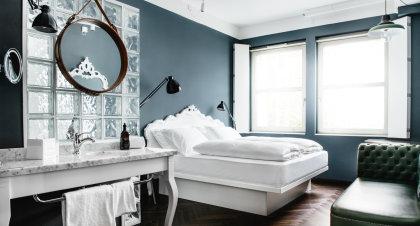 Standard+ Zimmer mit weißem Kingsize-Bett und dezenten Dekoelementen.