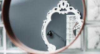 Ein mit Ledergurten umrandeter Spiegel im Standard+ Zimmer.