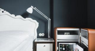 Reichhaltige Getränkeauswahl in der Minibar mit Ledermantel und daneben gleich das Doppelbett.