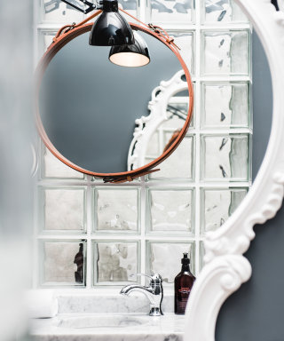 Classic Adnet-style mirror with leather framing above the washbasin.