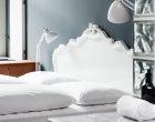 Standard Zimmer mit weißem Kingsize-Bett und dezenten Dekoelementen.