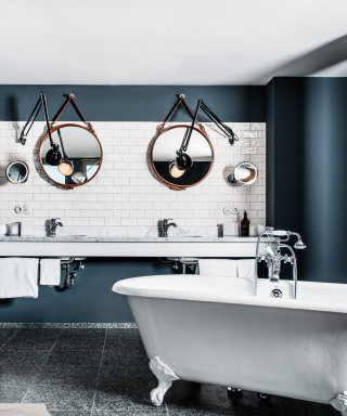 Two washbasins with modern designer mirror and a freestanding bathtub in front of it .