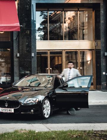 Ein Mann steigt in den schwarzen Maserati vor dem Grand Ferdinand Hotel.